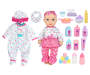 Light Skin Baby Doll with Blue Eyes Wearing a Cupcake Shirt Pink Tutu and Chevron Pattern Pants among Cupcake and Polka Dot Pajamas and Care Accessories Out of Package Overhead View Silo Image