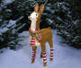 Light Up Tinsel Llama 31 Inches High with peppermint stripe scarf and legs quarter side view in outdoor setting environment image
