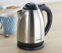 Stainless Steel Cordless Kettle 1.7 Liters on a Table with Cut, spoon and plate of cookies accent room setting environment image